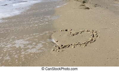 Painted heart in the sand on the beach washes off a wave,...
