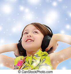 Little girl listening to music headphones. - Closeup...