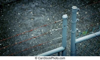 Barbed Wire Fence In Rainstorm - Industrial barb wire fence...