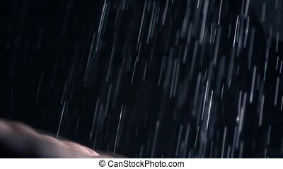 Super slow motion video of shower drops hitting a man's palm...