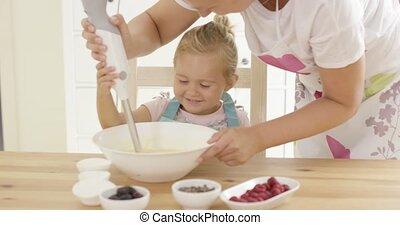 Pretty little blond girl learning to bake helping her mother...