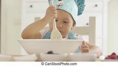 Adorable serious toddler at mixing bowl