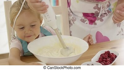 Cute happy little girl helping with the baking - Cute happy...