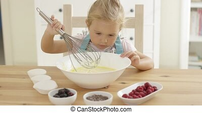 Girl looking at muffin batter with whisk - Cute little blond...