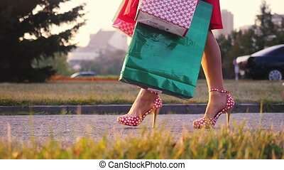 Women leg in beautiful dress with shopping bags goes on the...