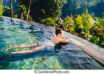 Young beautiful woman in outdoors swimming pool. Holiday concept with woman sunbathing in infinity swimming pool
