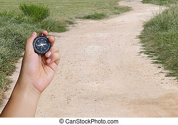 hand of a man holding a compass and road in the countryside....