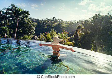 sexy woman enjoying the sun at infinity summer swimming pool at luxurious resort