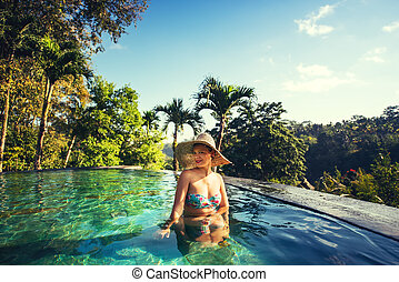 beautiful lovely brunette girl enjoying a sunny day at infinity pool