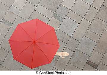 Red umbrella and a hand of man standing on stone floor and...