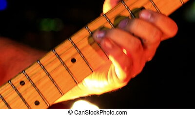 Guitarist Touches Electric Guitar Neck Strings in Night Bar