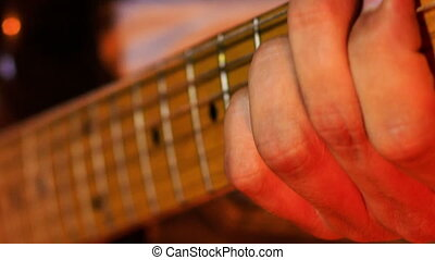Closeup Guitarist Runs Fingers over Neck Strings in Night...
