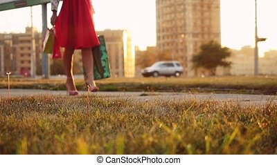 Young woman in beautiful dress with shopping bags goes on the street through the sun during sunset in slowmotion. 1920x1080