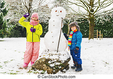 Two adorable kids playing together in snow park, wearing warm winter clothes