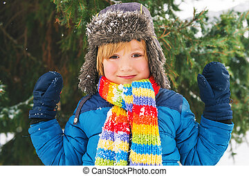 Winter portrait of a cute little boy under the snowfall,...