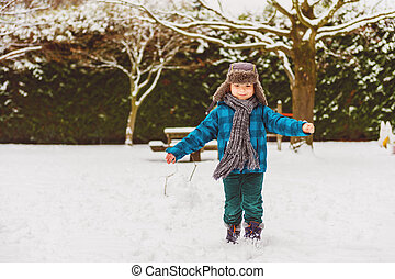 Cute little boy playing in winter park. Kid having fun...