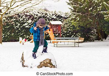 Cute little boy playing in winter park Kid having fun...