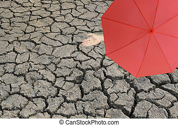 Red umbrella and a hand of man standing on cracked earth and...