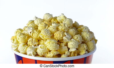 Popcorn with taste of bacon rotates on a white background. Close up shot
