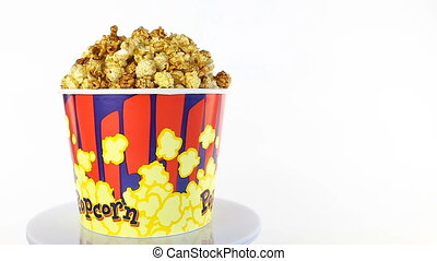 Caramel popcorn rotates on a white background. Wide shot
