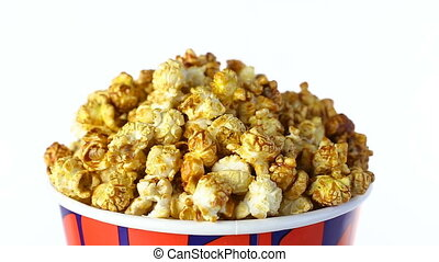 Caramel popcorn rotates on a white background. Close up shot