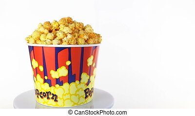 Cheese popcorn rotates on a white background. Wide shot