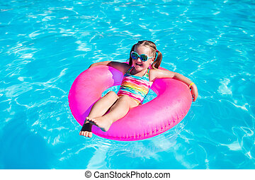 Little girl with toy ring in swimming pool - Happy little...