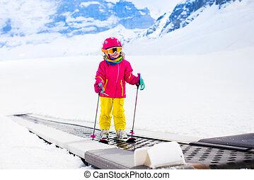 Child on ski lift - Child on magic carpet ski lift going...