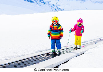 Child on ski lift - Children on magic carpet ski lift going...