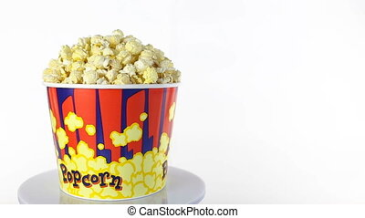 Salty popcorn rotates on a white background. Wide shot -...