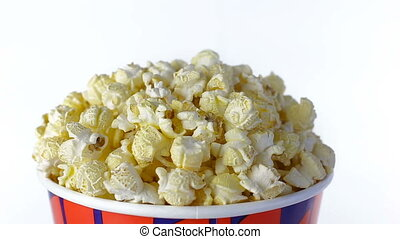 Salty popcorn rotates on a white background. Close up shot -...
