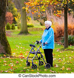 Senior lady with a walker in autumn park - Happy senior...