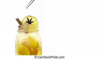 Hand made citrus lemonade rotates on a white background