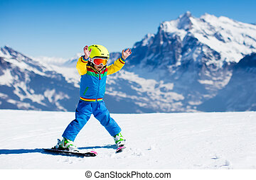 Little child skiing in the mountains - Child skiing in...