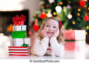 Little girl opening presents on Christmas morning - Family...