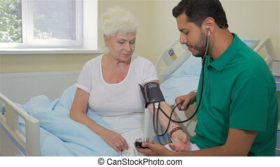 Doctor measures blood pressure of senior woman - Young...