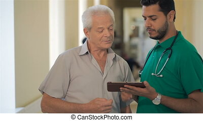 Doctor shows something on his tablet to senior man -...