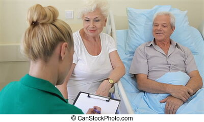 Nurse notes the state of health of senior male patient -...