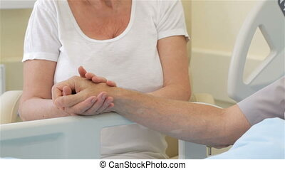 Senior woman strokes the hand of her ill husband - Senior...