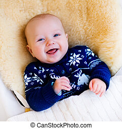 Little baby in nordic sweater on sheepskin muff - Funny...