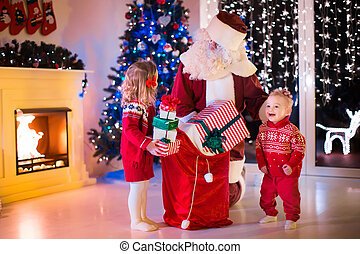 Kids and Santa opening Christmas presents - Children and...