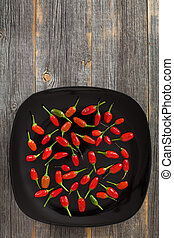 Red and green hot peppers on a black plate old wooden boards...