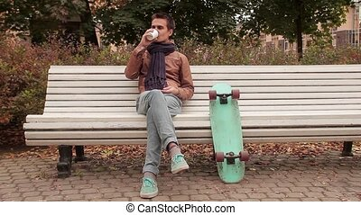 Young man with knitted scarf with skateboard sitting on...