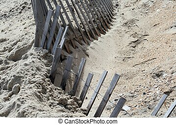 Wooden fence on sandy beach - a weathered wooden fence on a...