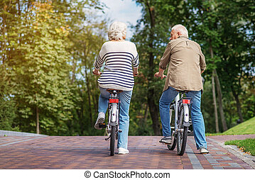 Mature man and woman cycling in nature - Old married couple...