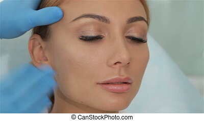Cosmetologist stretches the skin on the temple of the client...