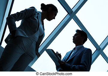 Interacting partners - Two silhouettes of businesspeople...