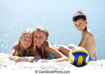 Rest - Photo of happy family lying on sand by water during...