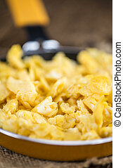 Scrambled Eggs in a Pan (selective focus) on wooden...