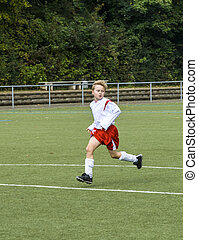 young soccer player runs over the football ground - young...